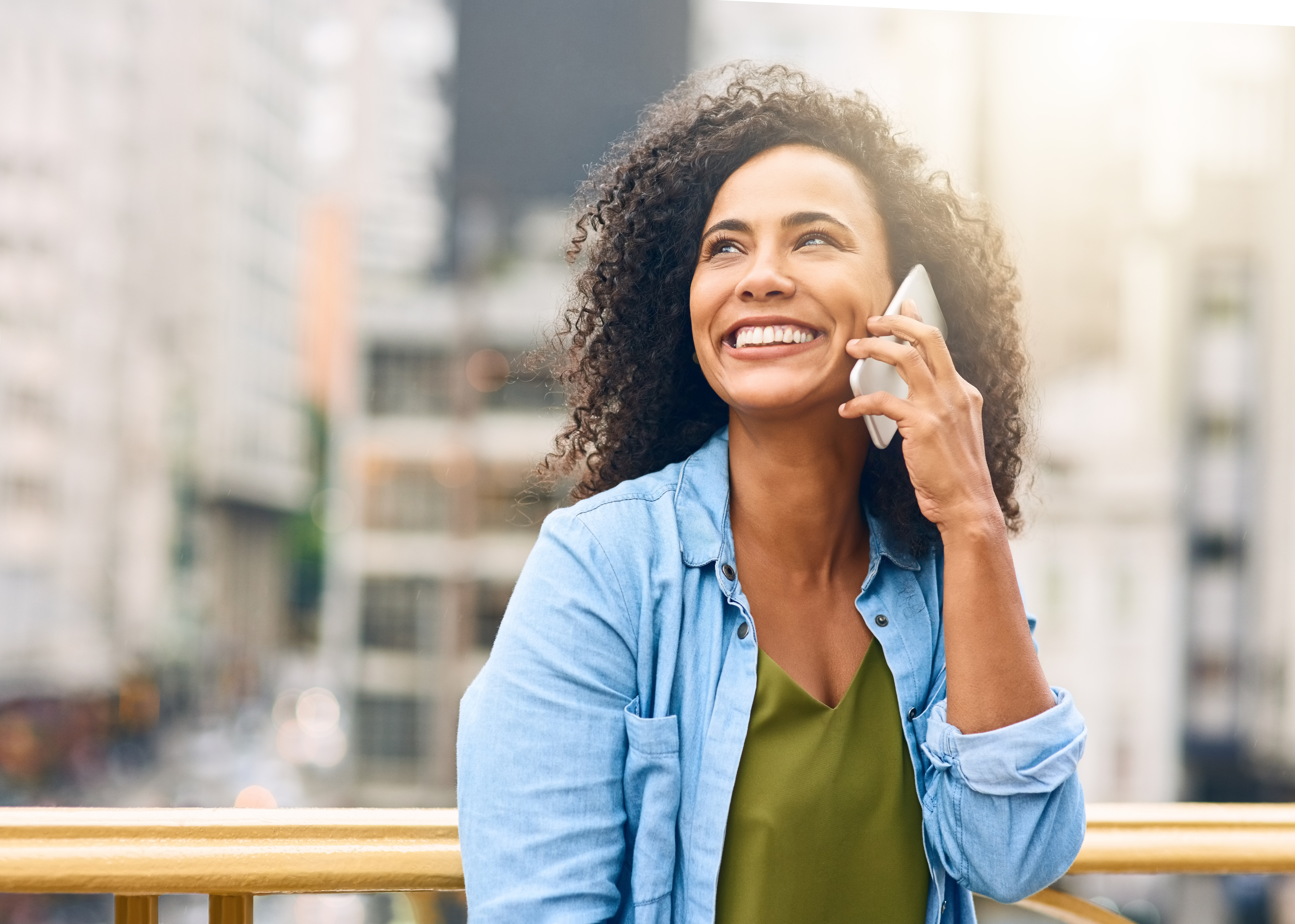 Woman in a city smiling and talking on the phone
